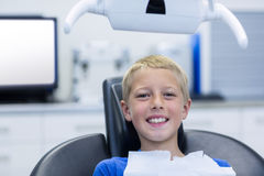 Smiling young patient sitting on dentist chair Stock Photo