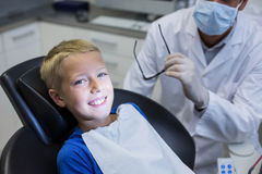 Smiling young patient sitting on dentist chair Stock Photography