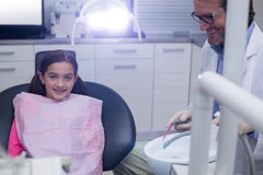 Smiling young patient sitting on dentists chair Royalty Free Stock Photos