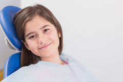 Smiling young patient sitting in dentists chair Royalty Free Stock Photo