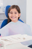 Smiling young patient sitting in dentists chair Stock Photography