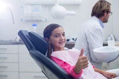Smiling young patient sitting on dentists chair Royalty Free Stock Photography