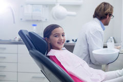 Smiling young patient sitting on dentists chair Stock Photos