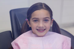 Smiling young patient sitting on dentists chair Royalty Free Stock Images