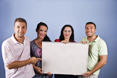 Smiling young people with add banner. Smiling young people holding a add banner and a man pointing to copy space, check also royalty free stock photo