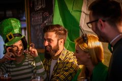 St Patrick`s Day Celebration - Friends in the Pub. Smiling young people drinking craft beer in pub on St Patrick`s Day holiday Royalty Free Stock Photo