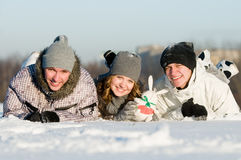 Smiling young people lying. Three smiling young people lying in snowdrift with rabbit at winter outdoors over blue sky Stock Image