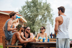 Smiling young people sitting and drinking together in summer Stock Photo