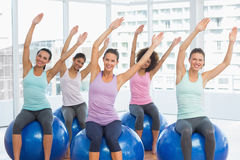 Smiling young people sitting on exercise balls Royalty Free Stock Photos