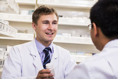 Smiling young pharmacist showing prescription medication to a customer Royalty Free Stock Photography