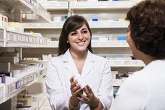 Smiling young pharmacist showing prescription medication to a customer Stock Image