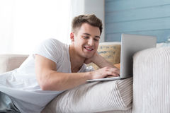 Smiling young positive man using laptop. Stock Images