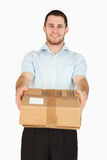 Smiling young post employee handing over parcel Stock Photography