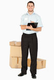 Smiling young post employee with parcels Royalty Free Stock Image