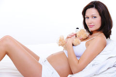 Smiling young pregnant female with teddy toy. Pretty smiling young pregnant female embrace the teddy toy Stock Photo