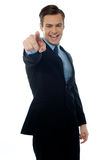 Smiling young professional pointing at you. Smiling young executive pointing at you in black suit on white background Stock Images