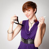 Smiling Young Red-Haired Woman Applying Makeup Royalty Free Stock Photos