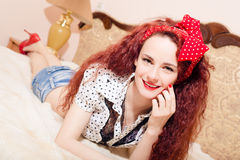 Smiling young redhead female lying on her belly Stock Photography