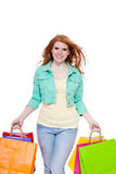 Smiling young redhead girl with colorful shoppingbags Royalty Free Stock Photography