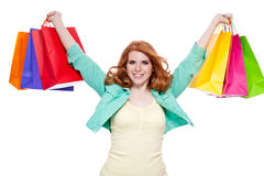 Smiling young redhead girl with colorful shoppingbags Royalty Free Stock Images