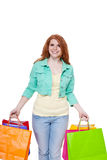 Smiling young redhead girl colorful shoppingbags Stock Images