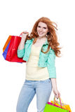 Smiling young redhead girl colorful shoppingbags Stock Photo