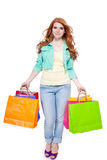 Smiling young redhead girl colorful shoppingbags Royalty Free Stock Photography