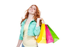 Smiling young redhead girl colorful shoppingbags Royalty Free Stock Photos