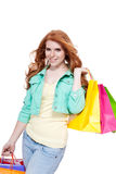 Smiling young redhead girl with colorful shoppingbags Stock Photo