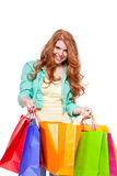 Smiling young redhead girl with colorful shoppingbags Stock Image