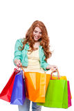 Smiling young redhead girl with colorful shoppingbags Stock Photography