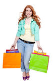 Smiling young redhead girl with colorful shoppingbags Royalty Free Stock Photos