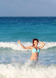 Smiling young redhead woman standing in the ocean Royalty Free Stock Photography