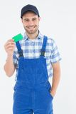 Smiling young repairman holding green card Royalty Free Stock Images