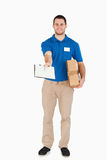 Smiling young salesman. With parcel asking for signature against a white background royalty free stock photo