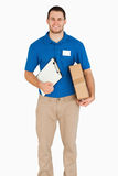 Smiling young salesman with packet and clipboard. Against a white background stock photo