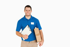 Smiling young salesman with parcel and clipboard. Against a white background royalty free stock photography