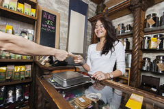 Smiling young salesperson accepting money from customer in tea store stock image