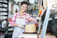 Smiling Young Saleswoman Slicing Cheese With Knife In Shop Royalty Free Stock Image