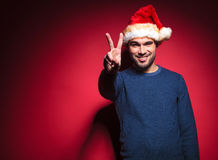 Smiling young santa showing the victory sign Stock Images