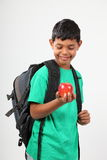 Smiling young school boy 10 holding red apple Royalty Free Stock Image