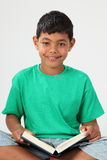 Smiling young school boy 10 reading a book. Young school boy, 10, sitting cross legged, wearing green t-shirt and reading a book Stock Images