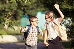 Smiling young school children in a school uniform against a tree Stock Photography