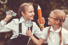 Smiling young school children in a school uniform against a tree Royalty Free Stock Photography