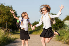 Smiling young school girls in a school uniform against a tree in. Smiling young school children in a school uniform jumping on the road in the park at the day Stock Photos