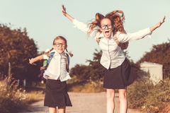 Smiling young school girls in a school uniform against a tree in. Smiling young school children in a school uniform jumping on the road in the park at the day Stock Photography