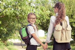 Smiling young school girls in a school uniform against a tree in Stock Photo
