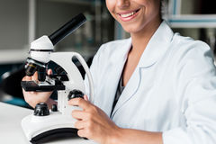 Smiling young scientist in white coat working with microscope in lab Royalty Free Stock Images