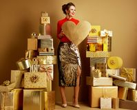 Smiling young shopper woman with golden heart looking aside royalty free stock photo