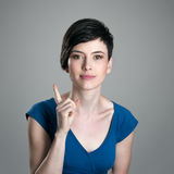 Smiling young short hair woman scolding finger looking at camera. Over gray studio background Stock Image